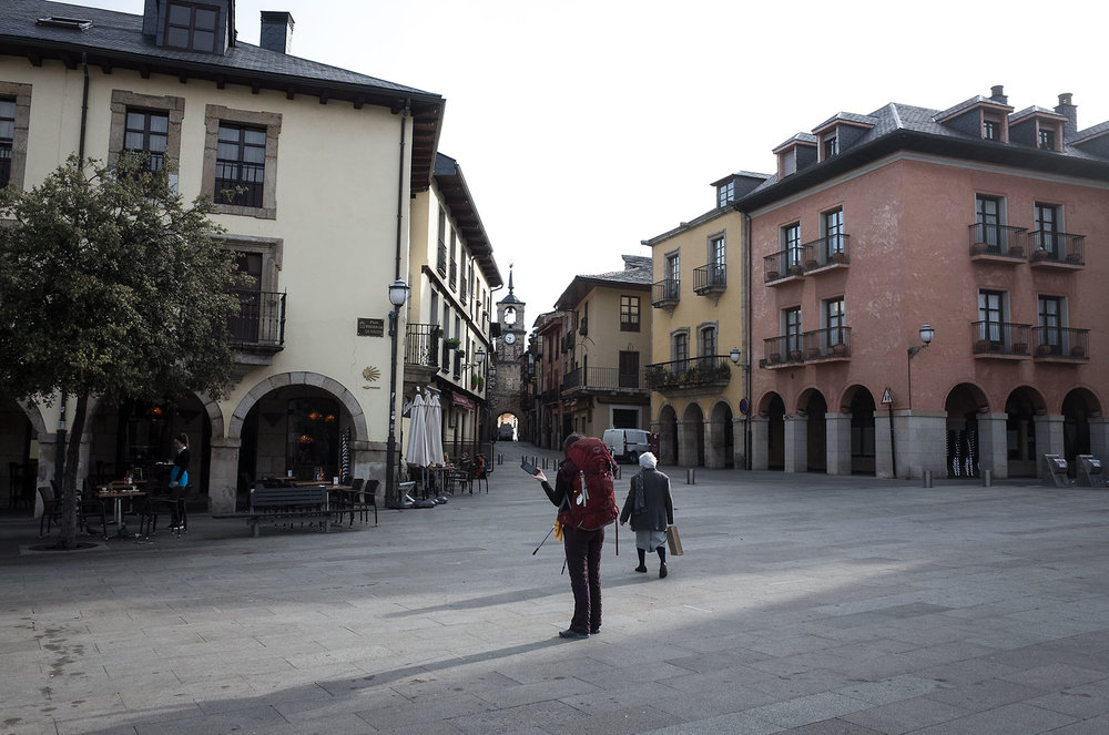 A pilgrim pauses to look for signage in Ponferrada. The Camino is marked by a series of seashell plaques and yellow arrows painted on buildings, traffic posts, curbs, and other urban surfaces.