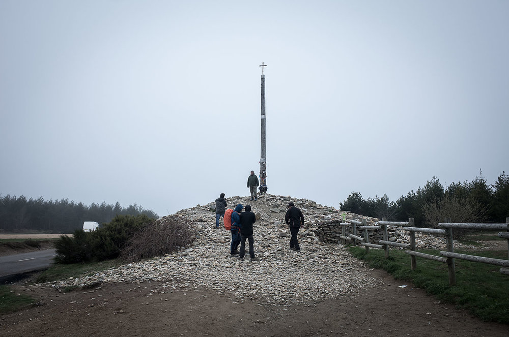 """The Cruz del Hierro represents the highest point on the Camino Frances. It is tradition for pilgrims to carry a small stone representing a emotional or spiritual burden in the pack. Upon reaching the Cruz, pilgrims deposit the stone and """"unburden"""" themselves."""