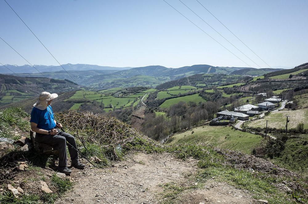 A pilgrim pauses for a break on the steep climb up to Alto do Poio.