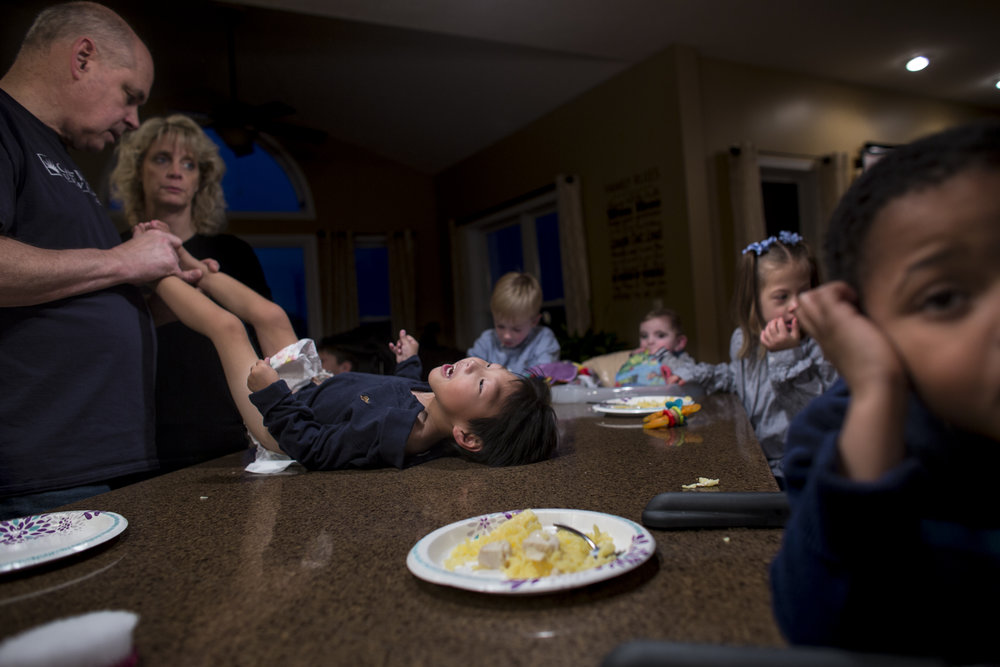 Barry changes Graham's diaper during a family dinner. The kitchen island is the center for all happenings of the Jencik family, from dinner, to diapers changes and minor medical procedures. Nov. 18, 2017