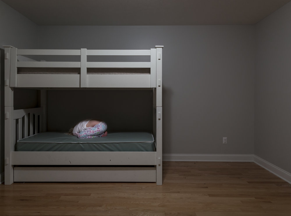 Tennyson (10) sleeps in her room. Her bare room is a safe haven away from the chaos of living with 13 other siblings. The lack of items that would be associated with a normal room is a necessity for Tennyson's safety. Nov. 17, 2017