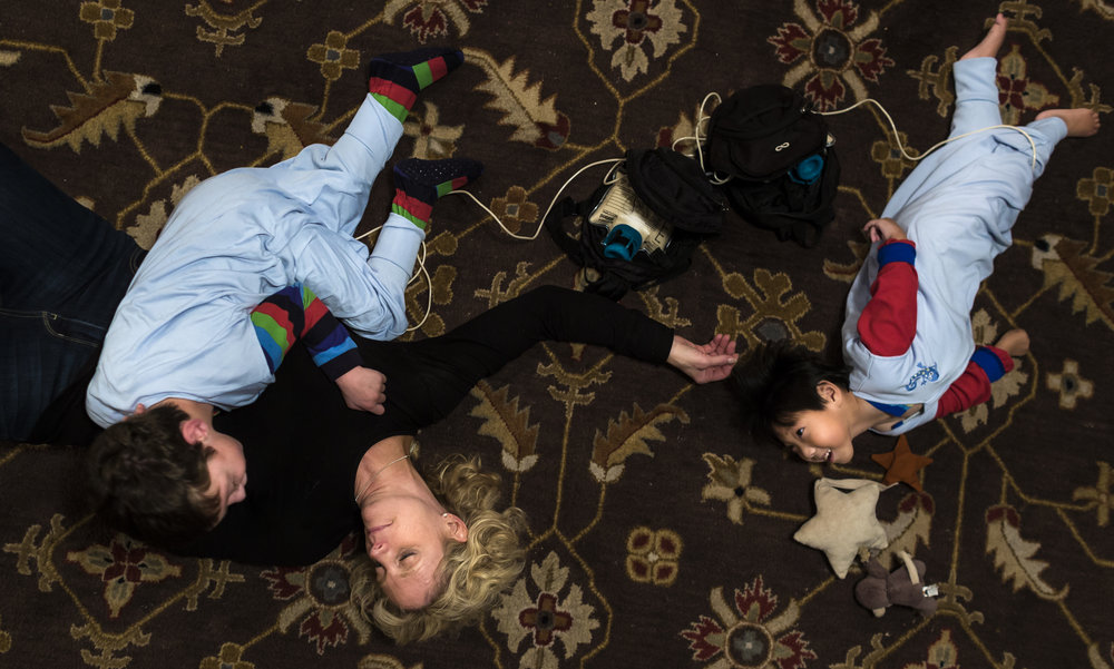 Brittany lays on her living room floor with her adopted sons Weston (7) and Graham (3). Both are being fed formula via a pump connected to their G-tubes. Nov. 18, 2017