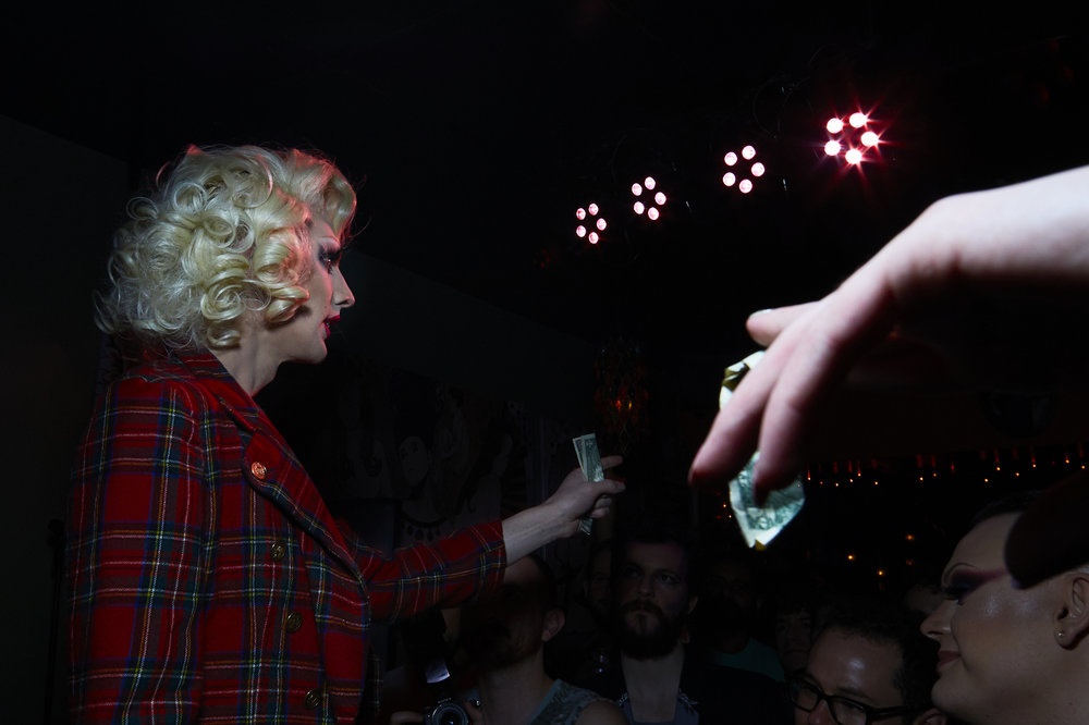 Judy Darling grabs cash tips from the audience.