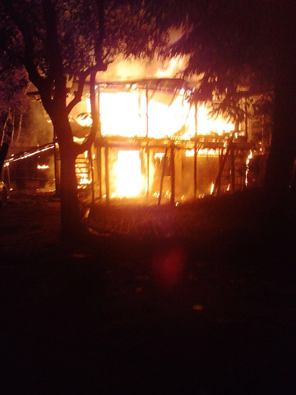 A Rohingya home burns during riots in the Arakan State of Burma.  *Cellphone images from surviving Rohingya refugees.  (not an image of Hasan's home)