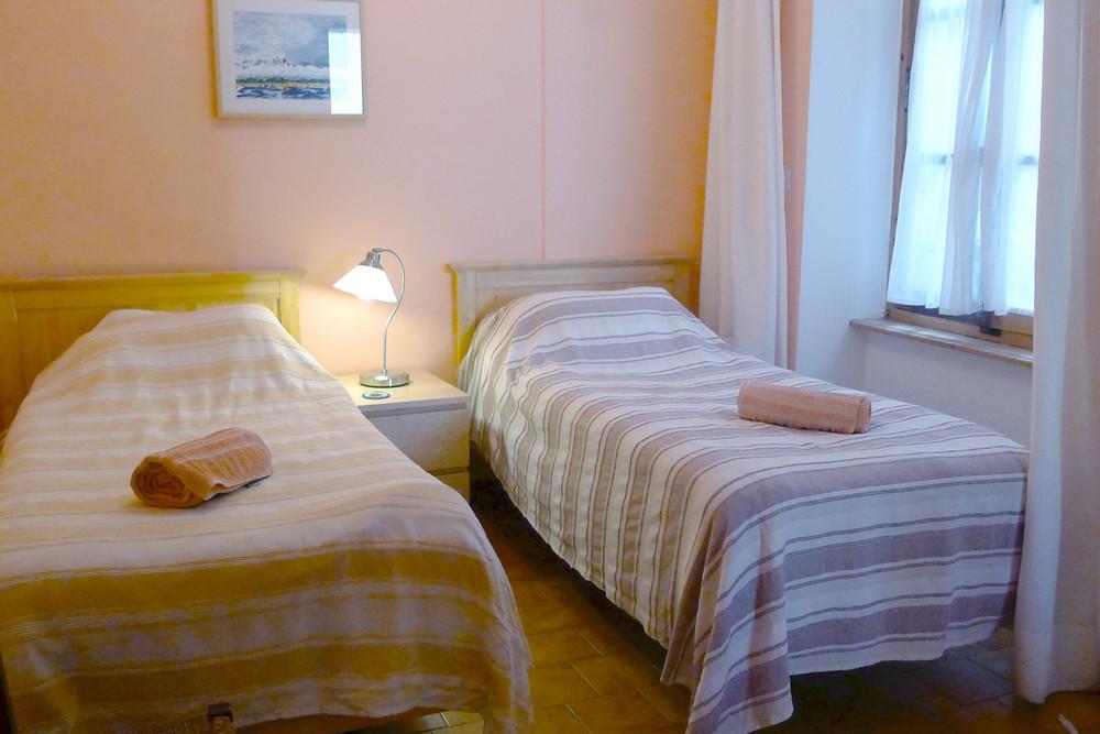 Das dritte Schlafzimmer hat zwei Einzelbetten und ein Fenster, das auf das Atrium herausgeht.