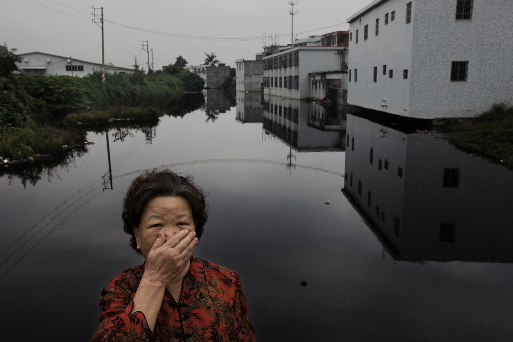 A woman from Ximei Village in Gurao, China. The economy of the area is centred around textile production, and many factories discharge pollution straight into local waterways like this one.   Photo credit: Lu Guanga / Greenpeace.
