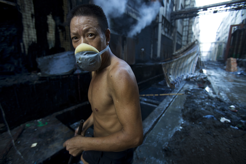 A worker at a Xintan jeans factory searches through wastewater, scooping out stones which are washed with denim in industrial washing machines to create the stonewash effect.  Image credit: © Lu Guang / Greenpeace