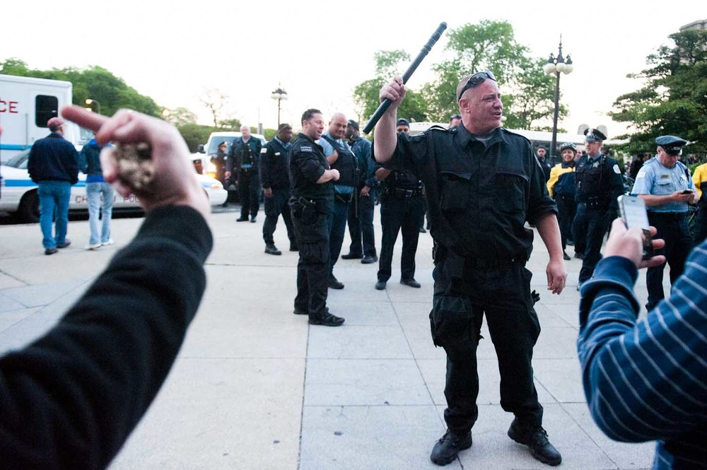 An unidentified Chicago Police officer waves his baton towards activists and calls them 'faggots' as a spontaneous march begins after police snatch a number of individuals from a resting crowd during the 2012 Occupy NATO demonstrations in Chicago, IL. (May 21st, 2012)
