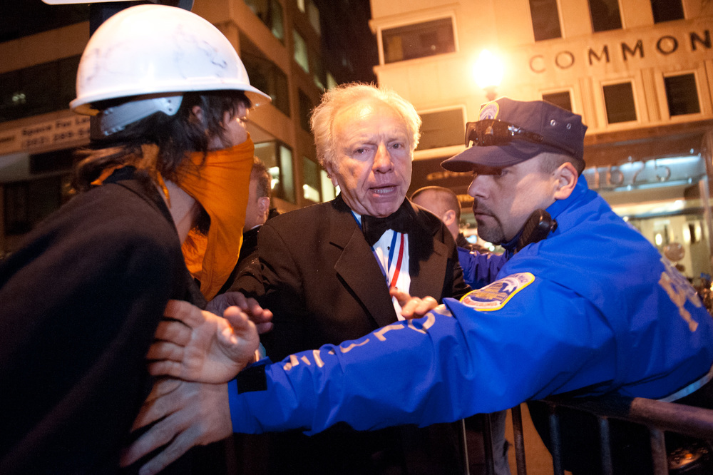 Joe Lieberman works past protestors to cross a police line on K St NW to join the Alfalfa Club dinner, a meeting for the highly affluentand wealthy on January 28th, 2012. The club's membership card, a gold medallion, can be seen around Lieberman's neck.