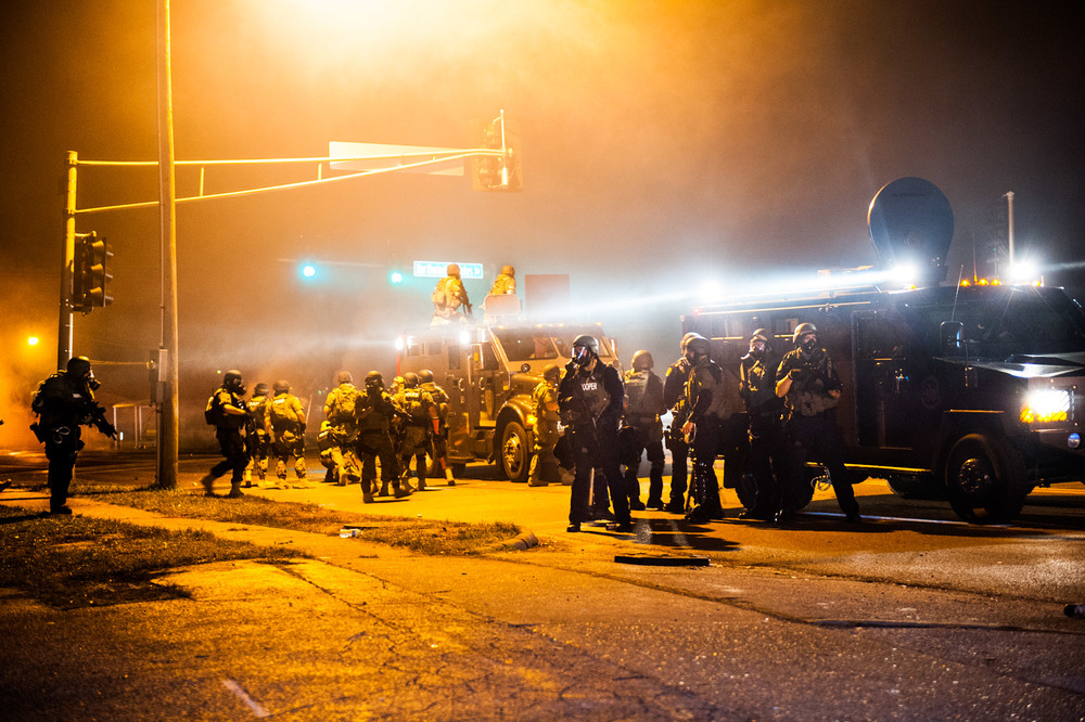 Officers of the Ferguson Police Department and Missouri State Police react to live fire during the August 2014 riots in Ferguson, MO after the slaying of Michael Brown.