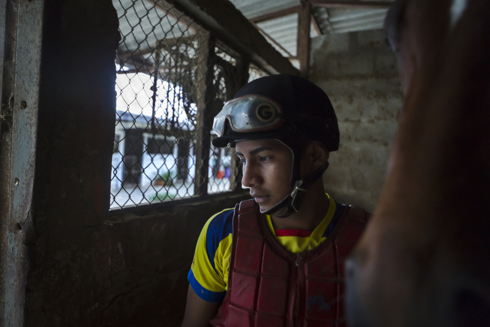Ronald González, a horse racing jockey, prepares for a day of practice early one morning at the Hippodrome Miguel Salem Dibo Racetrack in Guayaquil, Ecuador. Most mornings before the sunrises, González, along with both of his brothers and other members of his family, can be found on the backs of horses, galloping down a stretch of the racetrack.