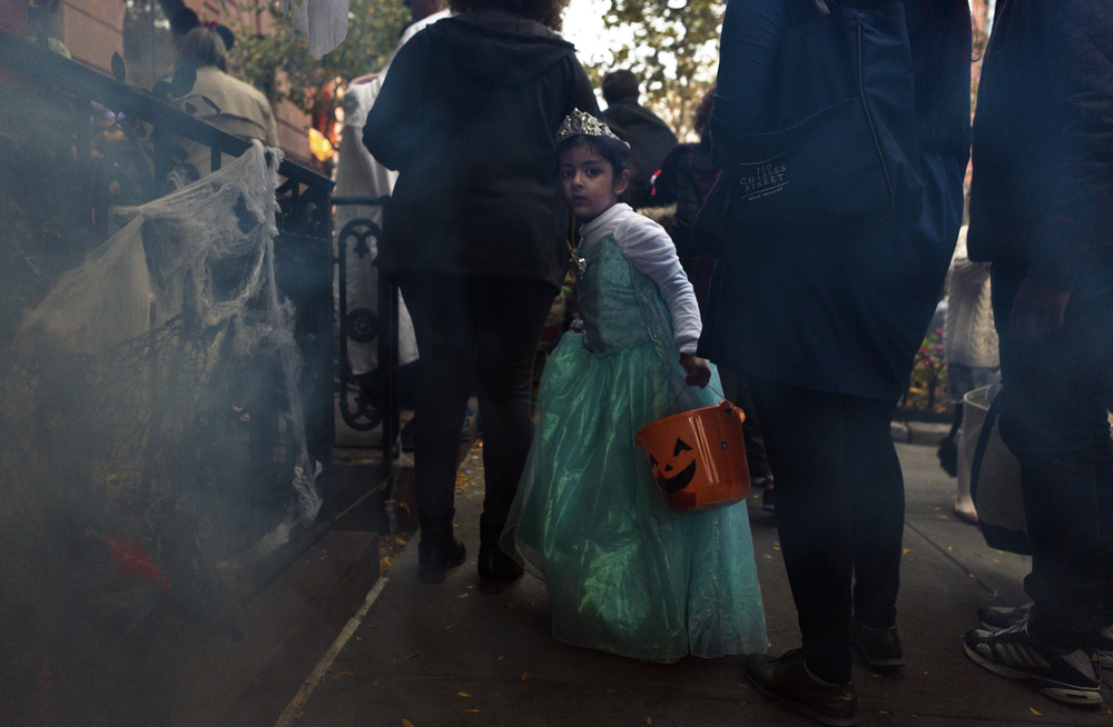 A child trick-or-treats on a smoky New York City street.