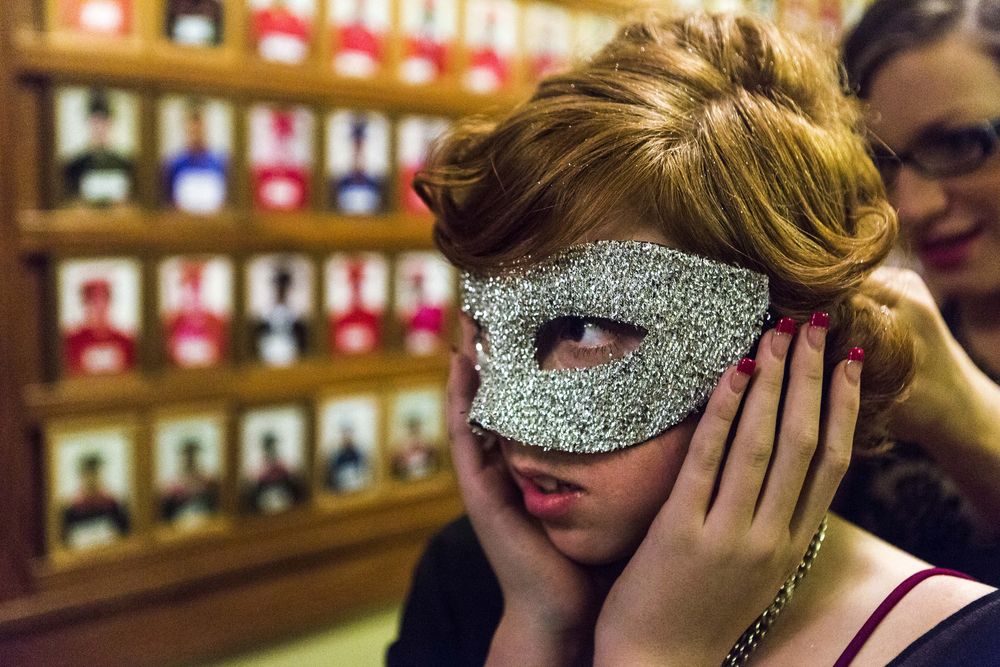 As part of her outfit, a teenager puts on a mask during the Lighthouse's Prom in Lincoln, Nebraska. Lighthouse, an organization that serves as a refuge for at-risk children for over 25 years, organized their own dance for those who could not afford to attend their school's prom. Everything from getting their nails to the the outfits themselves were donated.