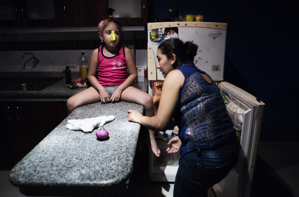 Michelle molds a nose out of Play-Doh while her mother, Amarilis Johanna Bayas Guevara, prepares dinner. Although Michelle cannot see and barely hear, she still does not like to be by herself.
