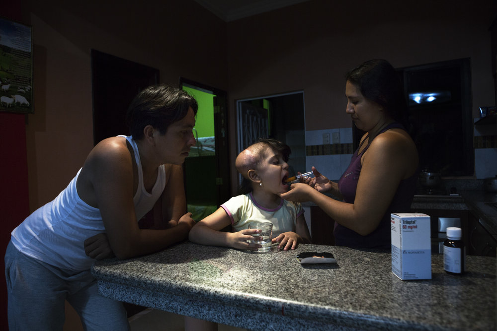 Michelle receives required medication from her parents in the kitchen of the family's home. Every three weeks, she goes through a 15-day radiation treatment, in hopes that her tumor will reduce in size.