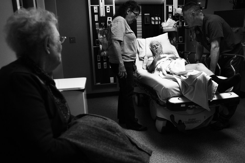 After falling one morning, Eloise and the couple's caretaker, Kathleen, check Ward into a local emergency room. He sits in a hospital bed, hands outstretched. Unable to assist her husband in the situation, Eloise sits in the corner of the hospital room, watching their caretaker and a doctor instead help Ward.