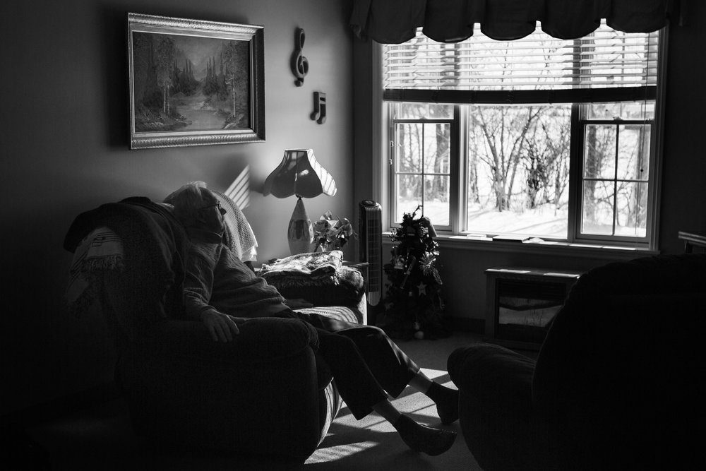 Ward sits in the couple's room. When he and his wife still lived in their home, Ward would sit outside and watch the squirrels and the birds play. His condition has declined since moving into the memory-care facility two years ago.