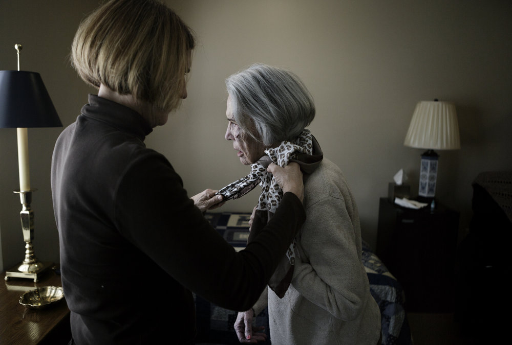 Nancy Olsson looks out her new bedroom window while her daughter, Jane, ties a scarf around her neck. Earlier in the morning, and with the help of her family, Nancy moved into an assisted living facility for those diagnosed with Alzheimer's disease.