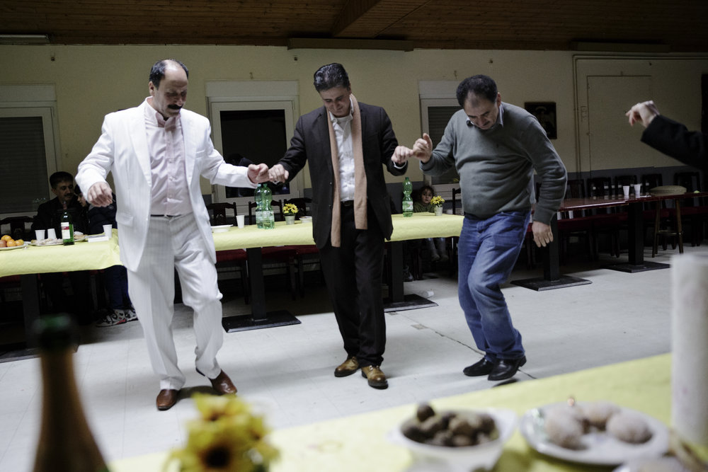 In front of German wooden wall hangings, Hatab dances with two of his brothers at the family's celebration of the Three Day Fast, one of the most important Êzidî holidays. For them, their celebration may be different than it used to be in Syria, but they are still together.