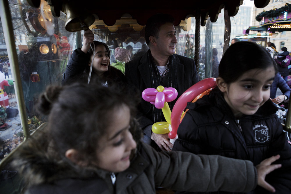 Hatab Omar rides a train with his children at a Christmas market in Hanover, Germany. He and his family are Êzidî, also known as Yazidi, an ethnic religious minority historically located in parts of Syria, Iraq and Turkey. Over the course of the last 16 years, nearly everyone in Hatab's family has left Syria and moved to Germany. His parents were one of the last members of his family to arrive to Germany in 2012.