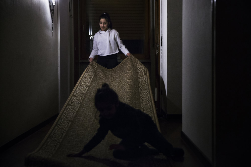 Hevi Omar, 13, plays with her brother, Moris, 4, in the entryway of the family's home. Because of either fear, discrimination, or the combination of both, many Êzidî individuals in recent history have decided to leave their homelands and to move to another county. Throughout the Êzidî's existence, they have been the target of 73 genocides.