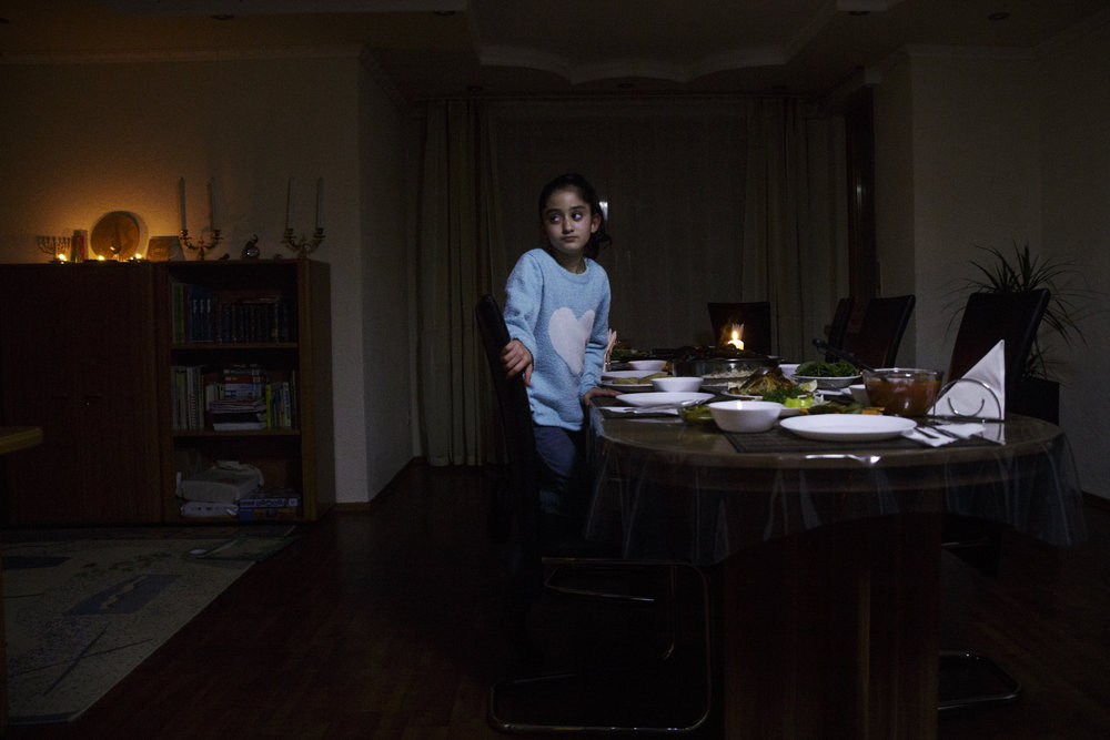 Lor waits for a family dinner after a day of fasting in December. The family believes in the importance of retaining one's religious history, as well as recognizing the significance of being involved with their surrounding community.