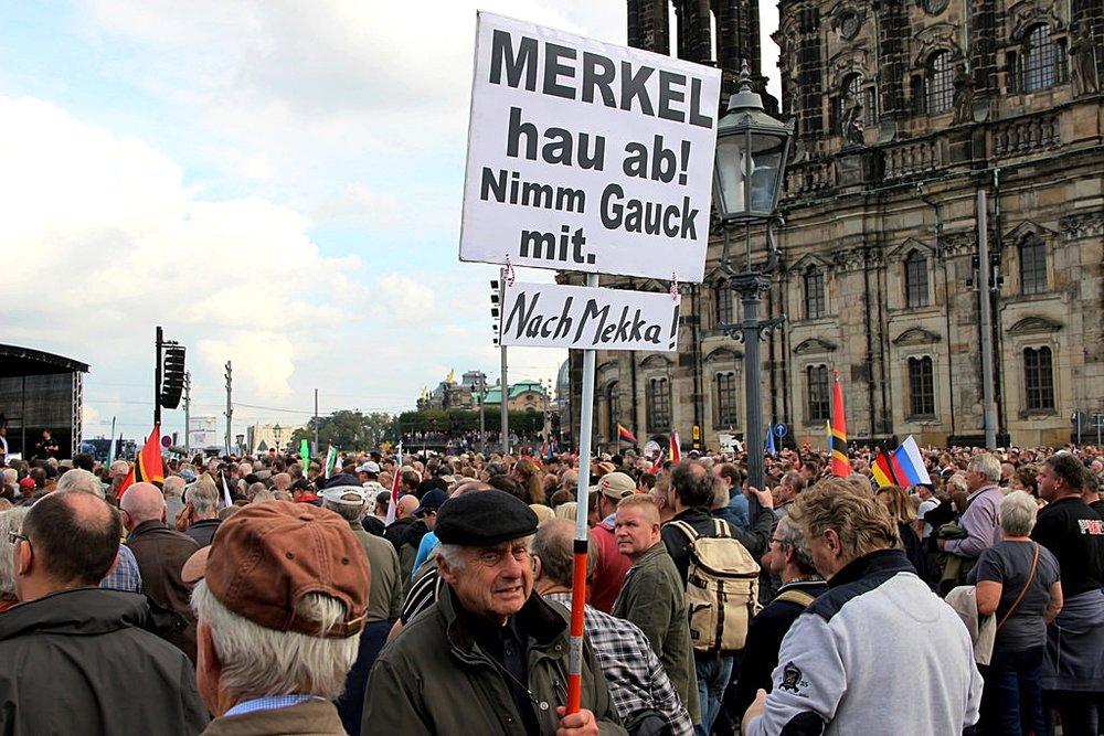 """Manifestazione anti-migrantii a Dresda (Sachsen), nel cartello """"Merkel va via e porta Gauck [ex-Presidente della Repubblica] con te verso la Mecca"""". Foto: strassentriche via photopin"""