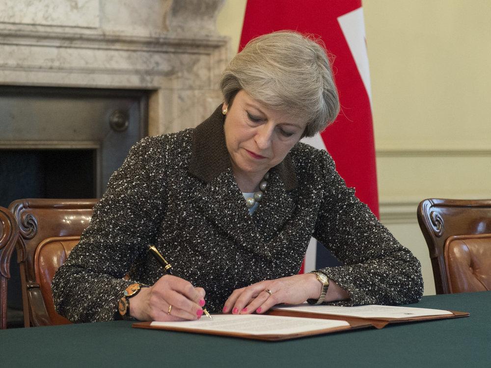 Theresa May mentre firma la lettera alla Commissione Europea. Foto: Prime Minister Office Licenza: CC 2.0