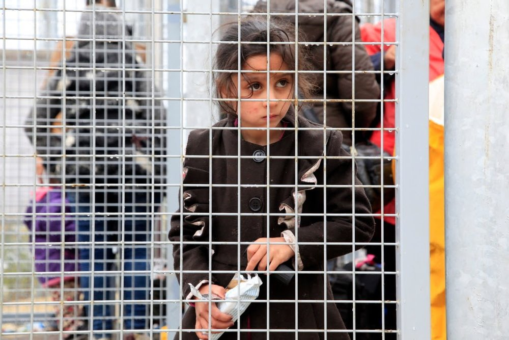 """Bambini reclusi nel centro di """"accoglienza"""" di Röszke, Ungheria. Nessun minorenne dovrebbe, per leggere, essere detenuto in uno di questi centri, come tale la misura è uno dei principali punti di accusa dell'Unione Europea contro Viktor Orban.Foto:Visit to Röszke and Tompa, Hungary di Rebecca Harms. Licenza:CC 2.0"""