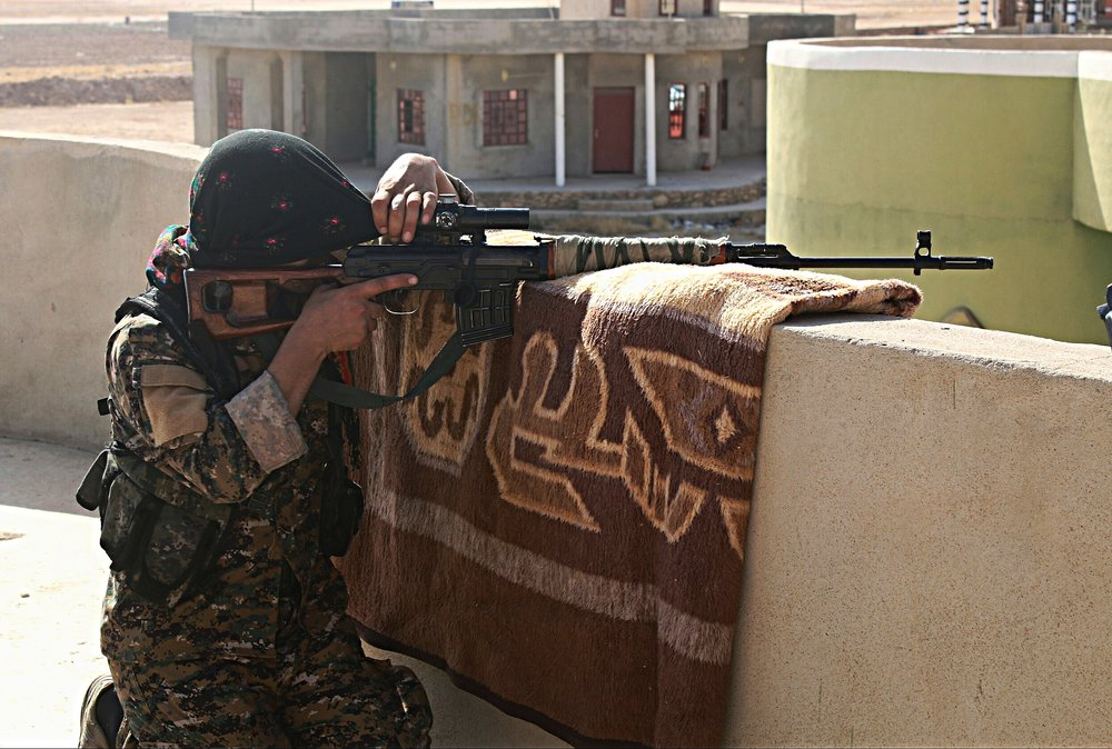 Soldato Yezida dell'YPJ, le milizie del Kurdistan siriano. Supportate dagli Stati Uniti, e con la copertura aerea della Russia, i Curdi stanno combattendo all'interno di Raqqa in quella che potrebbe essere l'ultima campagna campale verso la sconfitta dell'ISIS. Rimangono aperte le altre domande: quale futuro per la regione dopo lo Stato Islamico? E, soprattutto, come affrontare la questione curda alla luce del referendum sull'indipendenza del Kurdistan iracheno e l'enorme territorio in mano all'YPJ in Siria? Foto: KurdishstruggleLicenza: CC 2.0