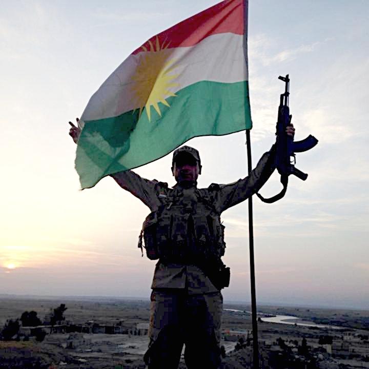 Un soldato curdo o Peshmerga accanto alla bandiera del KRG, il governo regionale del Kurdistan iracheno che si accinge a cercare l'indipendenza. Foto: KurdishstruggleLicenza: CC 2.0