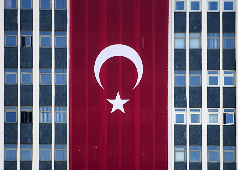 La bandiera turca esposta su un palazzo in supporto al Presidente Erdogan dopo il fallito colpo di stato del 15 luglio 2016, una visione ormai normale nel paesaggio urbano di Ankara ed Istanbul. Foto:  Chairman of the Joint Chiefs of Staff Licenza:  CC 2.0