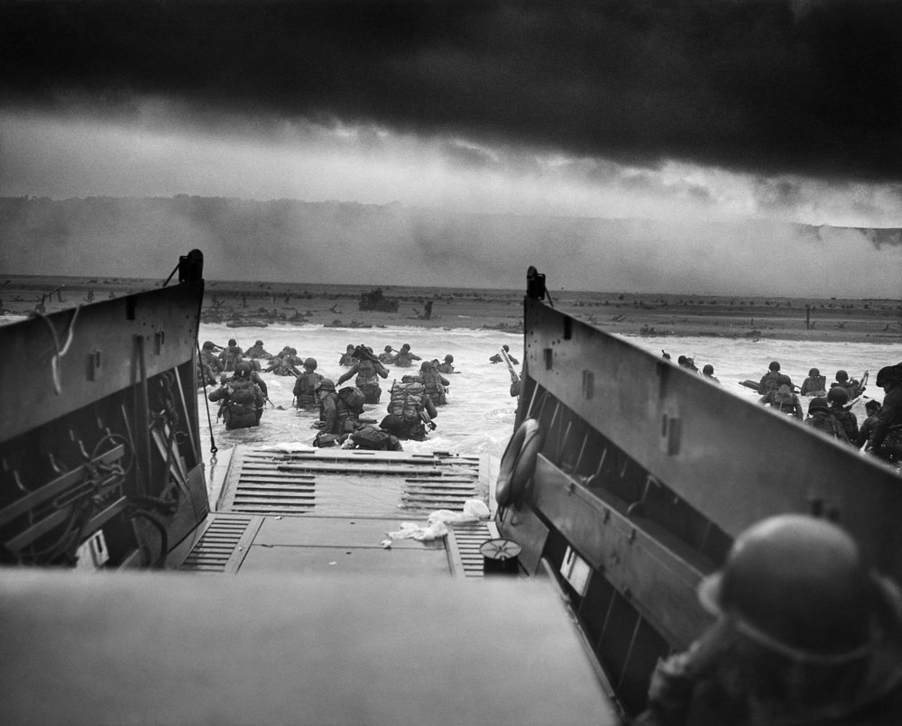 A LCVP (Landing Craft, Vehicle, Personnel) from the U.S. Coast Guard-manned USS Samuel Chase disembarks troops of Company E, 16th Infantry, 1st Infantry Division (the Big Red One) wading onto the Fox Green section of Omaha Beach (Calvados, Basse-Normandie, France) on the morning of June 6, 1944. American soldiers encountered the newly formed German 352nd Division when landing. During the initial landing two-thirds of the Company E became casualties.  by  Chief Photographer's Mate (CPHoM) Robert F. Sargent