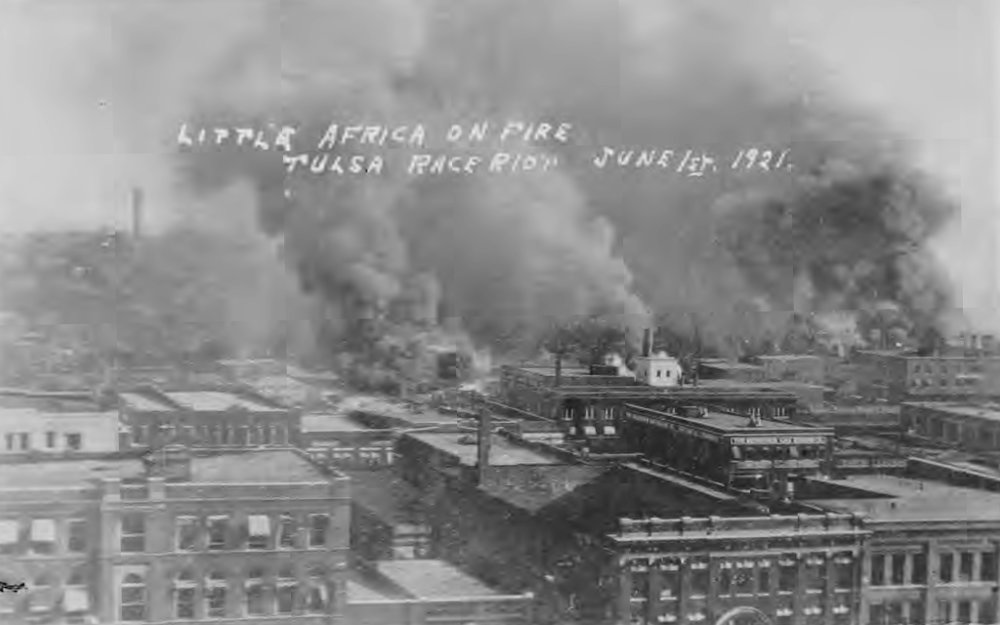 Little Africa on Fire. Tulsa Race Riot, June 1, 1921.  Taken from roof of Hotel Tulsa on 3rd St. bt. Boston and Cincinnati Avenues.  The first row of buildings is along 2nd Street.  Smoke cloud on left is where the fire started (Cincinnati Ave. and the Frisco Tracks).  This image is from a postcard in the collection of McFarlin Library, University of Tulsa