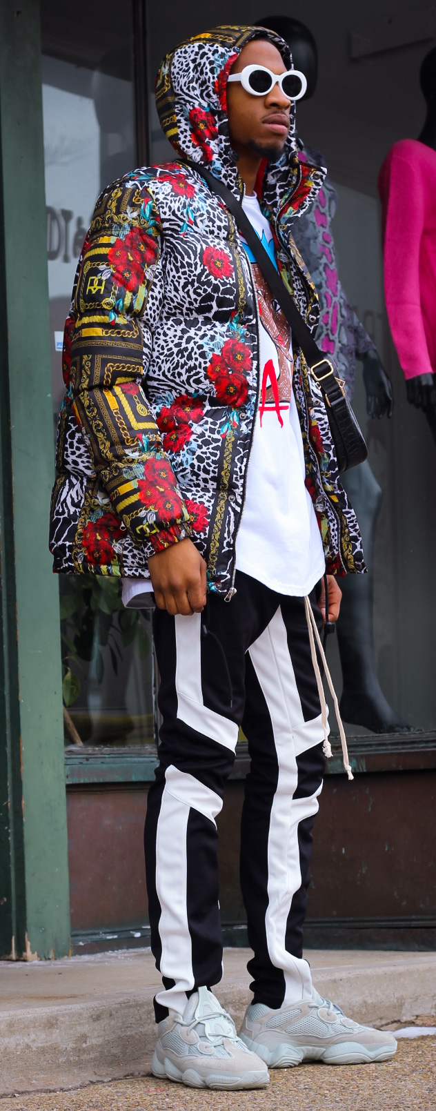 Floral Chains Puffer Jacket & Sing Bag by Reason  Joggers by EPTM  Tee by Cooper9  Sunglasses available in store  Model: Eli   Photo by Maik Mur   Styled by Giovanni Centurione