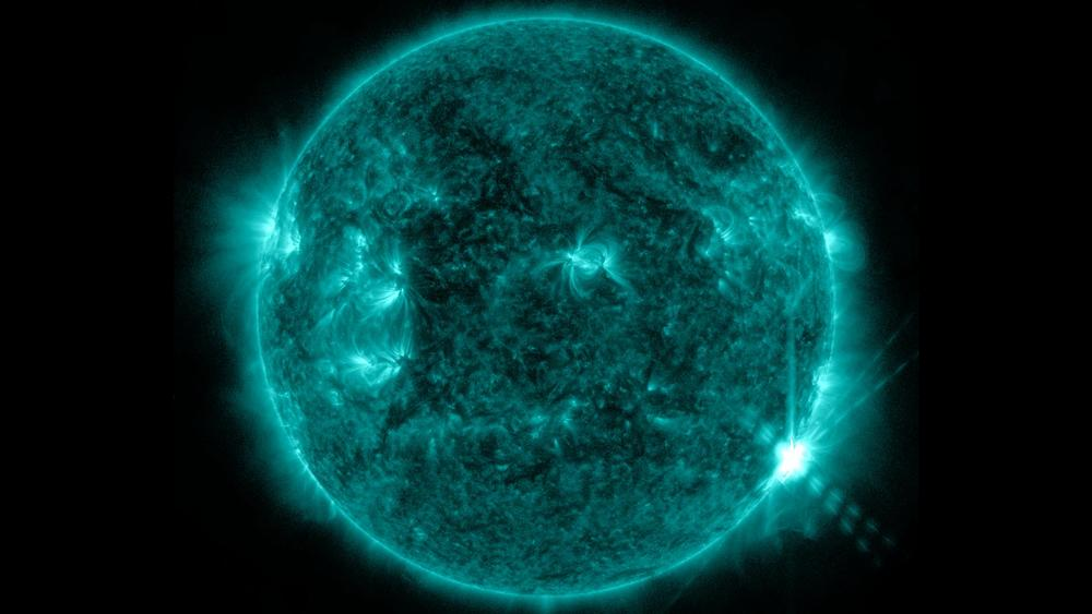 An M-class flare appears on the lower right of the sun on June 7, 2013. This image was captured by NASA's Solar Dynamics Observatory in the 131 Angstrom wavelength, a wavelength of UV light that is particularly good for seeing flares and that is typically colorized in teal. Caption: NASA/SDO