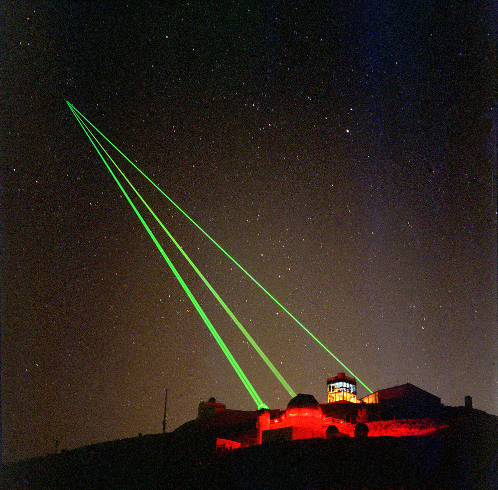 Three green lasers are seen emanating from facilities at the Starfire Optical Range on Kirtland Air Force Base, New Mexico. Lasers and deformable optics are used here to eliminate or minimize optical distortions caused by the Earth's atmosphere. Image Credit: US Air Force
