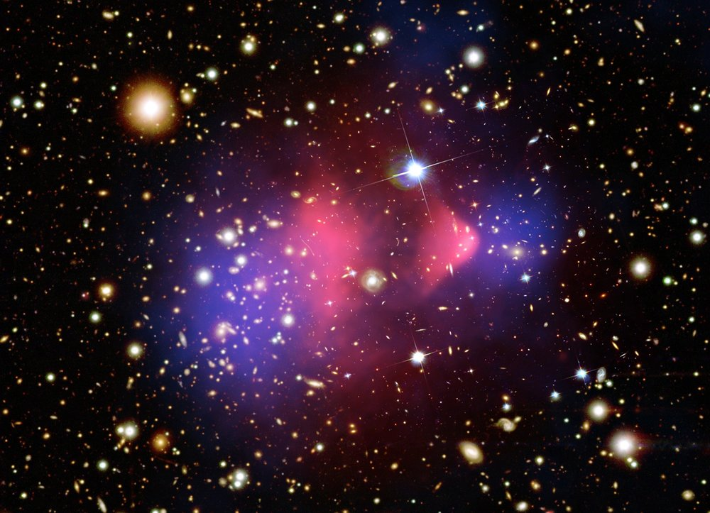 The Bullet Cluster. Dark purple indicates the location of the visible + dark matter mass. Red shows the X-ray emitting gas. Individual galaxies are seen in the optical image. Image credits: X-ray: NASA/CXC/CfA/ M.Markevitch et al.; Lensing Map: NASA/STScI; ESO WFI; Magellan/U.Arizona/ D.Clowe et al., Optical: NASA/STScI; Magellan/U.Arizona/D.Clowe et al