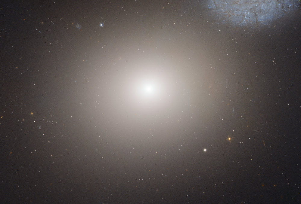 This is a Hubble Space Telescope image of the massive elliptical galaxy M60. The galaxy lies about 50 million light-years away inside the immense Virgo Cluster of 2,500 galaxies. A portion of the faint bluish spiral galaxy NGC 4647 can be seen in the upper right corner of this image. Image Credit: NASA, ESA, and the Hubble Heritage (STScI/AURA)-ESA/Hubble Collaboration