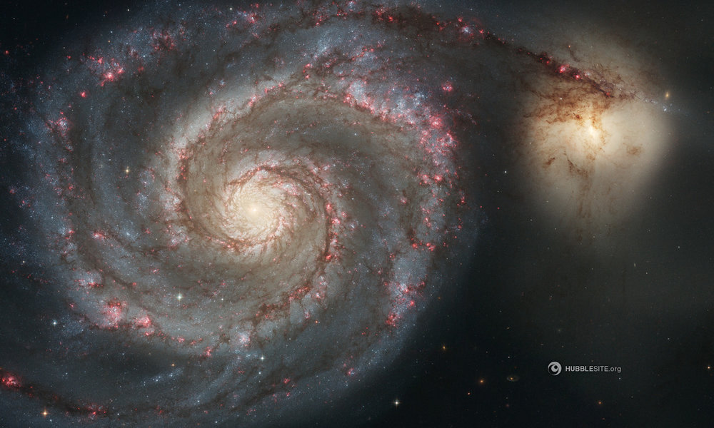 The large Whirlpool Galaxy (left) is known for its sharply defined spiral arms. Their prominence could be the result of the Whirlpool's gravitational tug-of-war with its smaller companion galaxy (right). Image Credit: NASA, ESA, S. Beckwith (STScI), and The Hubble Heritage Team (STScI/AURA)