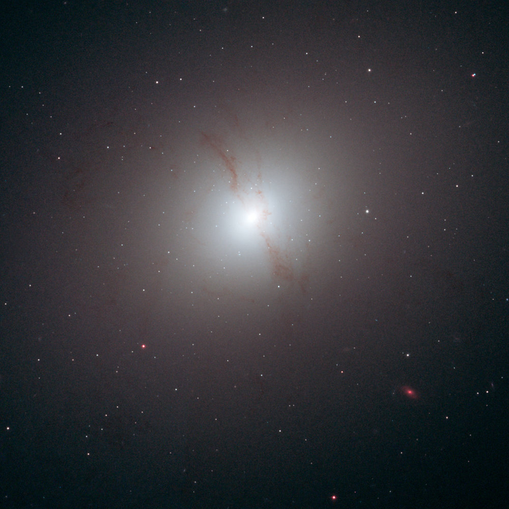 The elliptical galaxy NGC 4589. A dust lane is visible going vertically through the cloud of stars that make up this galaxy. Image Credit: NASA, ESA, and R. Foley (University of Illinois)