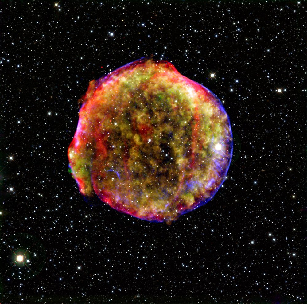 This composite image of a supernova remnant combines infrared and X-ray observations. The explosion left a blazing hot cloud of expanding debris (green and yellow). The location of the blast's outer shock wave can be seen as a blue sphere of ultra-energetic electrons. Newly synthesized dust in the ejected material and heated pre-existing dust from the area around the supernova radiate at infrared wavelengths of 24 microns (red). Foreground and background stars in the image are white. Image Credit: MPIA/NASA/Calar Alto Observatory.