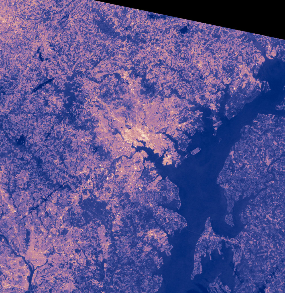 This image shows the approximate temperature of the land surface (how hot the land would be to the touch) on a summer's day in Baltimore, Maryland. The highest temperatures are yellow, while cool temperatures are deep purple. The image was made from data collected by the Landsat satellite on August 1, 2001. Image credit: NASA, Robert Simmon, caption text Holli Riebeek