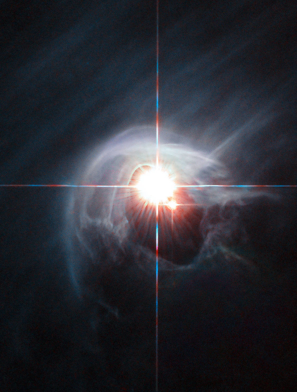 Two stars shine through the center of a ring of cascading dust in this image taken by the NASA/ESA Hubble Space Telescope. The star system is named DI Cha, and while only two stars are apparent, it is actually a quadruple system containing two sets of binary stars. As this is a relatively young star system it is surrounded by dust. The young stars are molding the dust into a wispy wrap. The host of this alluring interaction between dust and star is the Chamaeleon I dark cloud — one of three such clouds that comprise a large star-forming region known as the Chamaeleon Complex. DI Cha's juvenility is not remarkable within this region. In fact, the entire system is among not only the youngest but also the closest collections of newly formed stars to be found and so provides an ideal target for studies of star formation. Image credit: ESA/Hubble & NASA, Acknowledgement: Judy Schmidt