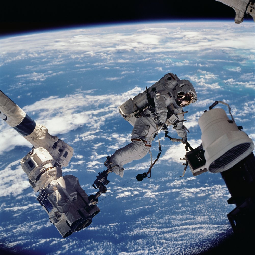 In this photo, Astronaut David A. Wolf, STS-112 mission specialist, anchored to a foot restraint on the Space Station Remote Manipulator System (SSRMS) or Canadarm2, carries the Starboard One (S1) outboard nadir external camera. Image credit: NASA