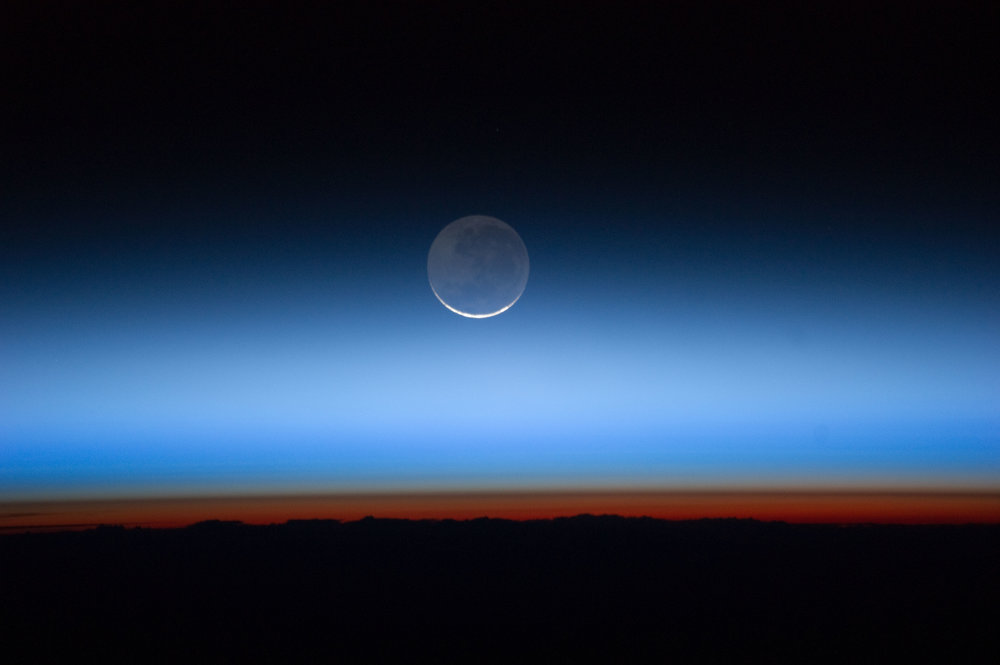 Photographed by an Expedition 28 crew member onboard the International Space Station, this image shows the moon at center, with the limb of Earth near the bottom transitioning into the orange-colored troposphere, the lowest and most dense portion of the Earth's atmosphere. Image credit: NASA