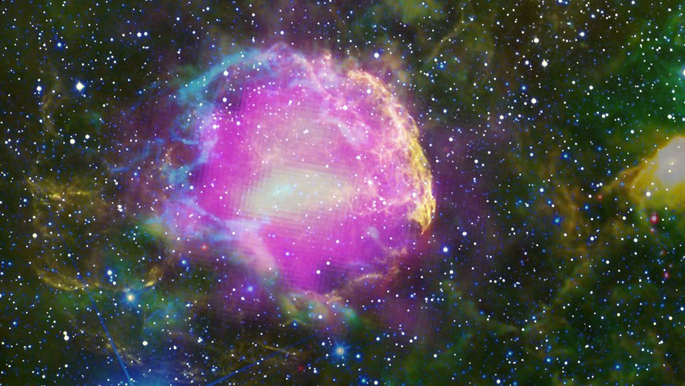 This multiwavelength composite shows the supernova remnant IC 443, also known as the Jellyfish Nebula. Fermi GeV gamma-ray emission is shown in magenta, optical wavelengths as yellow, and infrared data from NASA's Wide-field Infrared Survey Explorer (WISE) mission is shown as blue (3.4 microns), cyan (4.6 microns), green (12 microns) and red (22 microns). Image credit: NASA/DOE/Fermi LAT Collaboration, Tom Bash and John Fox/Adam Block/NOAO/AURA/NSF, JPL-Caltech/UCLA