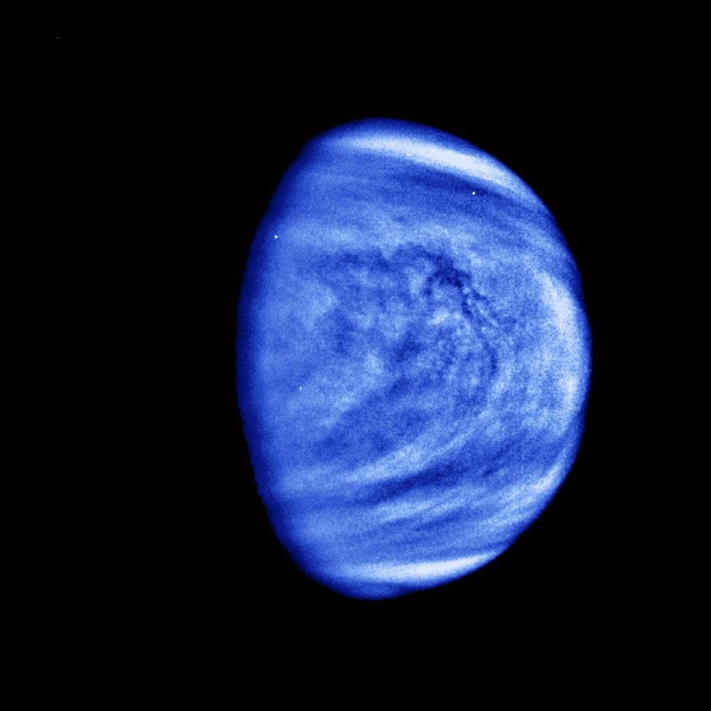 This picture of Venus was taken by the Galileo spacecraft's Solid State Imaging System on February 14, 1990, at a range of almost 1.7 million miles from the planet. A highpass spatial filter has been applied in order to emphasize the smaller scale cloud features, and the rendition has been colorized to a bluish hue in order to emphasize the subtle contrasts in the cloud markings and to indicate that it was taken through a violet filter. Image credit: NASA/JPL