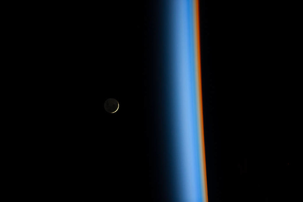 On Feb. 1, 2014, Japan Aerospace Exploration Agency astronaut Koichi Wakata tweeted this view of a crescent moon rising and the cusp of Earth's atmosphere. Distinct colors are visible because the dominant gases and particles in each layer of the atmosphere act as prisms, filtering out certain colors of light. Image credit: NASA.