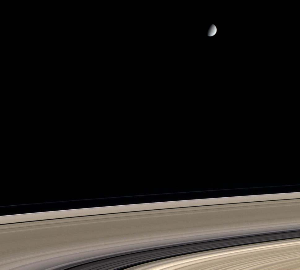 Saturn's icy moon Enceladus hovers above Saturn's exquisite rings in this color view from Cassini. The rings, made of nearly pure water ice, have also become somewhat contaminated by meteoritic dust during their history, which may span several hundred million years. Enceladus shares the rings' nearly pure water ice composition.  Image credit :  NASA/JPL